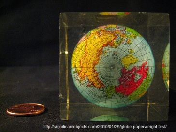 penny next to globe paperweight